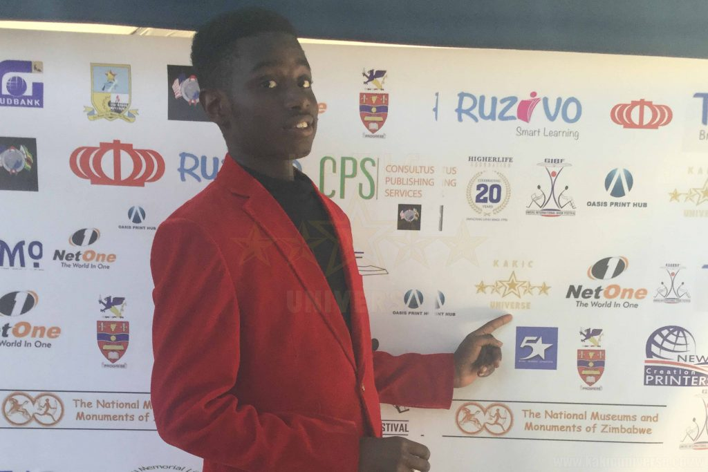 Kudakwashe Maxwell posing infront of the banner of participants at the GIBF 2017